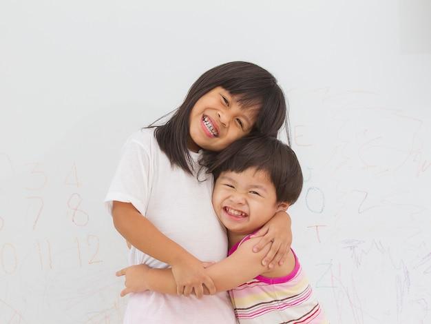 Kleine jongen en meisje knuffelen op muur achtergrond