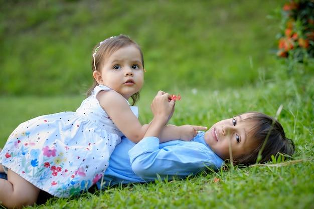 Kleine jongen en meisje liggend op een groene weide.