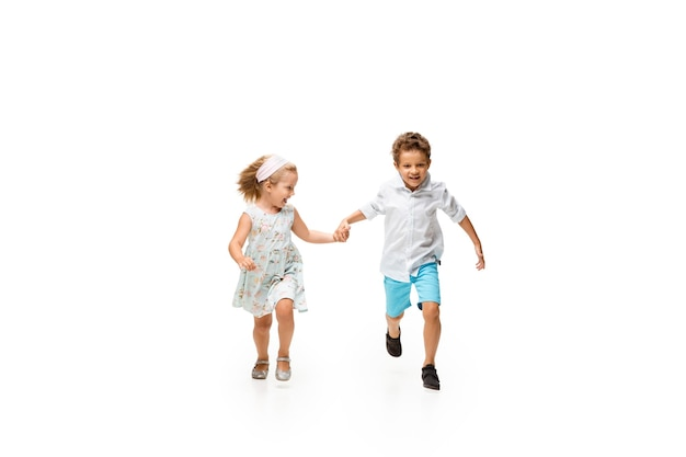 Kleine jongen en meisje lopen op een witte achtergrond, happy