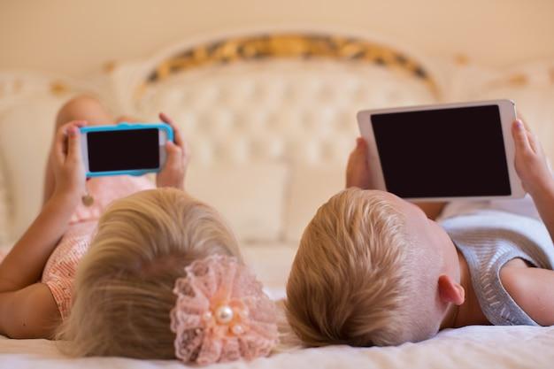 Kleine jongen en meisje met gadgets op bed