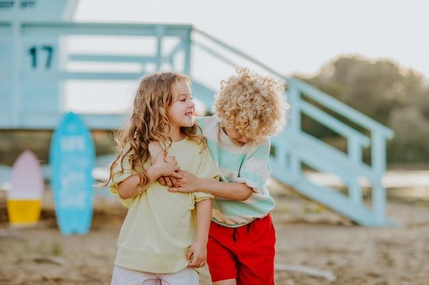 Kleine jongen en meisje met zomerkleren knuffelen op het strand met badmeestertoren op de achtergrond