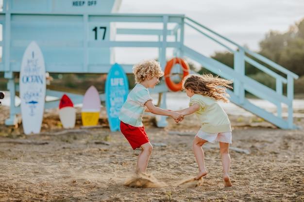 Kleine jongen en meisje met zomerkleren spelen op het strand met badmeestertoren op de achtergrond