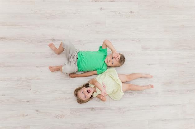 Kleine jongen en meisje op de vloer liggen.
