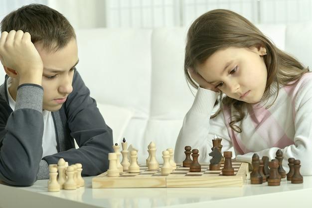 Kleine jongen en meisje schaken thuis. kinderen spelen schaken