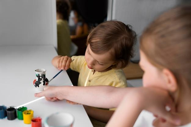 Kleine jongen en meisje schilderen samen vaas thuis