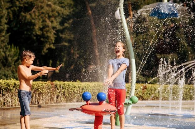 Kleine jongen en meisje spelen met spatten op waterspeeltuin in zomer park. kinderen vrije tijd in aquapark, wateravontuur