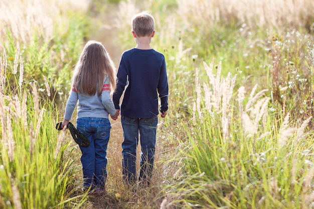 Kleine jongen en meisje staande hand in hand