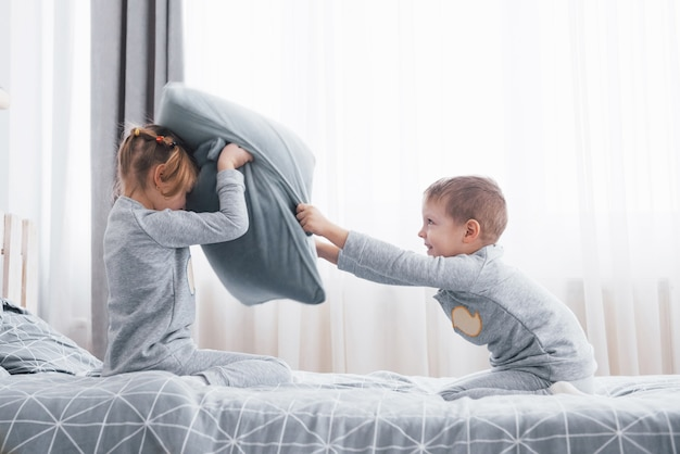Kleine jongen en meisje voerden een kussengevecht op op het bed in de slaapkamer. stoute kinderen sloegen elkaar op kussens. ze houden van dat soort spellen.