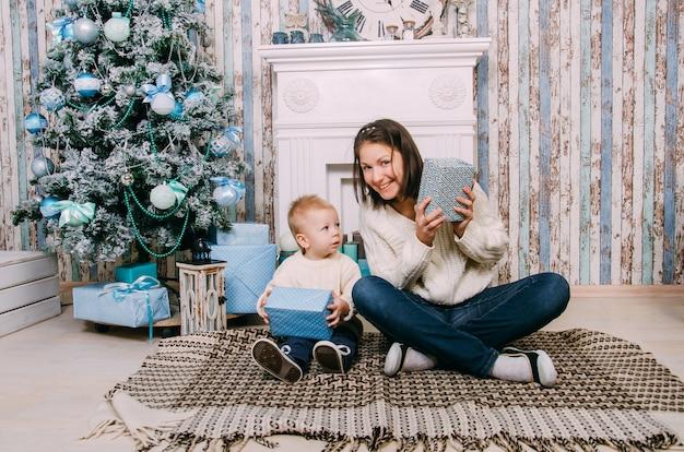 Kleine jongen en moeder in de buurt van de kerstboom