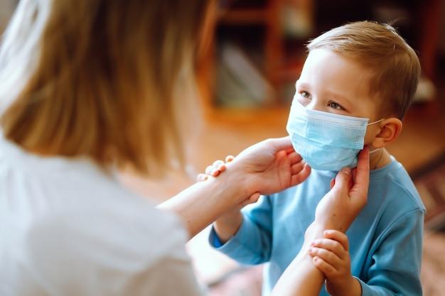 Kleine jongen en moeder in medisch masker.