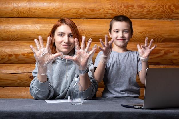 Kleine jongen en moeder trekken chirurgische wegwerphandschoenen aan en maken zich klaar om thuis chemische experimenten te doen