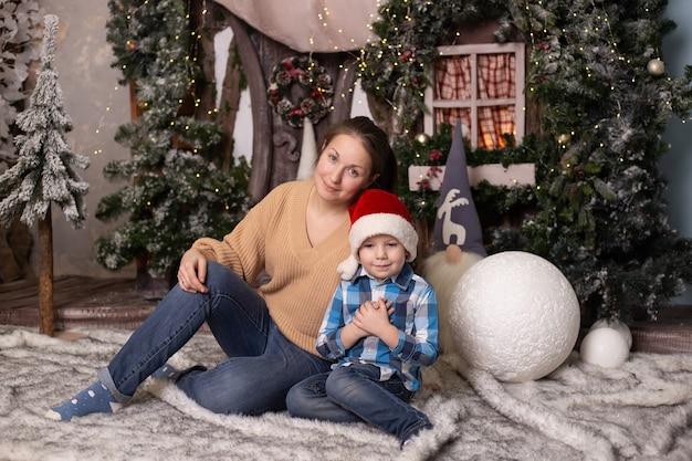 Kleine jongen en zijn moeder in de buurt van kerstboom, speelgoedhuis en kabouters.