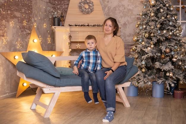 Kleine jongen en zijn moeder thuis in de buurt van open haard en kerstboom.