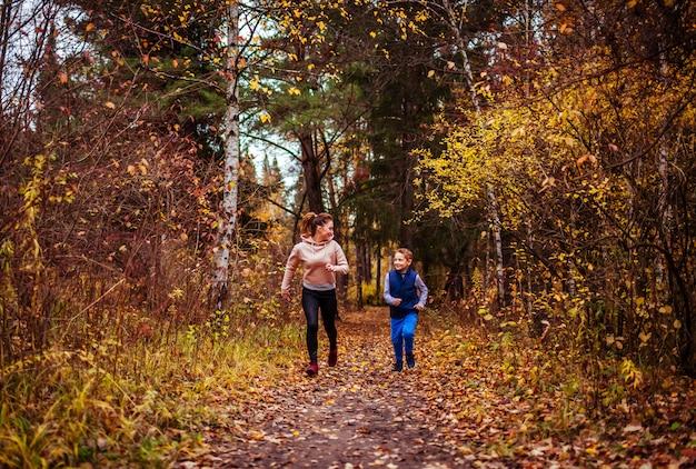 Kleine jongen en zijn zus uitgevoerd in herfst bos