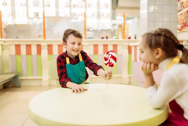 Kleine jongen geeft handgemaakte lolly aan meisje. kinderen in werkplaats bij patisserie leren karamel maken. vakantieplezier in de snoepwinkel