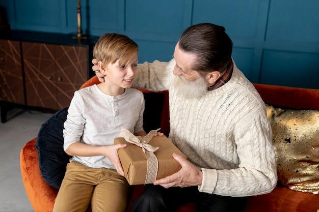 Kleine jongen geeft zijn grootvader een geschenk