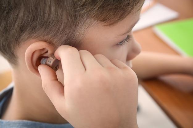 Kleine jongen gehoorapparaat invoegen
