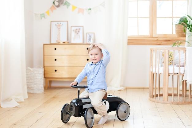 Kleine jongen. gelukkig kind rijden speelgoed vintage auto. grappig kind thuis spelen. zomer en reizen concept. actieve kleine jongen autorijden pedaal in de kinderkamer. peuter besturen van een retro-auto, jongen in speelgoedauto