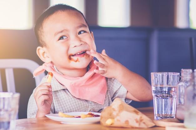 Kleine jongen geniet van het eten van frietjes met zijn handen en saus op de lip