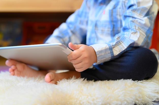 Kleine jongen heeft een tablet in zijn handen