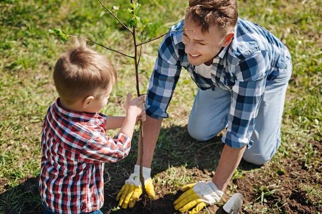 Kleine jongen helpt zijn glimlachende vader om een nieuwe fruitboom te planten in de tuin van een landhuis