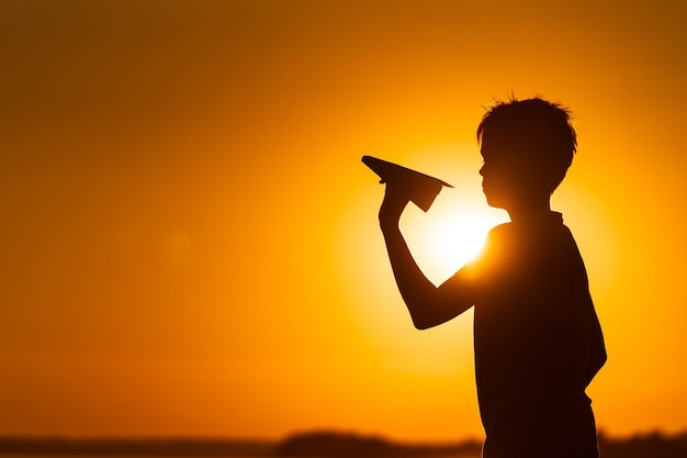 Kleine jongen houdt een papieren vliegtuigje in zijn hand bij de rivier bij een prachtige oranje zonsondergang in de zomer