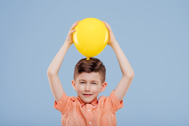 Kleine jongen houdt gele ballon omhoog. kijkt naar de camera, geïsoleerd op een blauwe achtergrond, kopieer ruimte