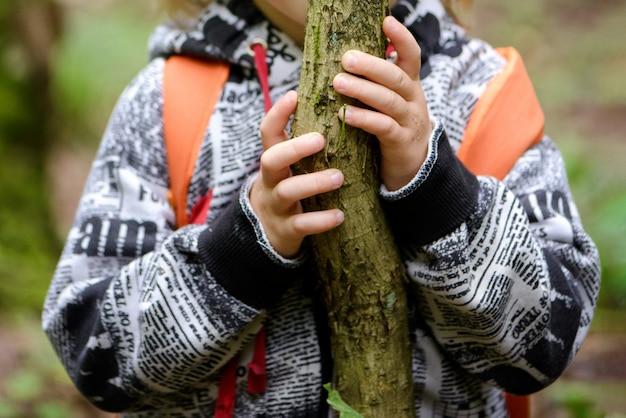 Kleine jongen houdt zich met zijn handen vast aan een dunne boomstam