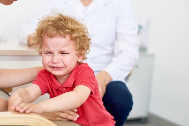 Kleine jongen huilen op kinderarts kantoor