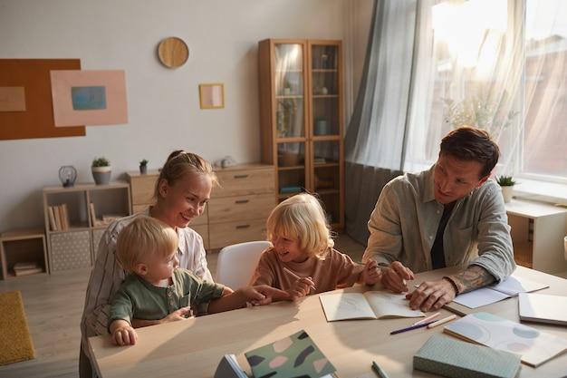 Kleine jongen huiswerk met vader terwijl moeder met baby zitten en spelen ze zijn in de woonkamer