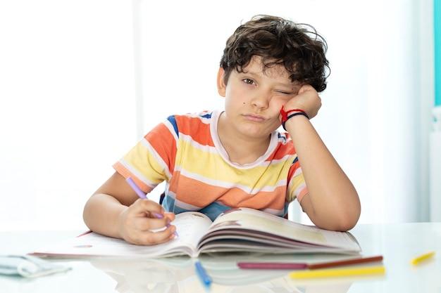 Kleine jongen huiswerk met verveelde uitdrukking