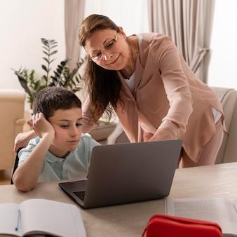 Kleine jongen huiswerk met zijn grootmoeder op laptop