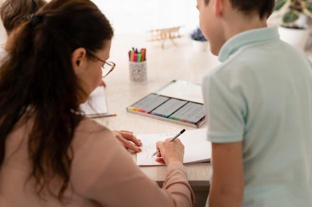 Kleine jongen huiswerk met zijn grootmoeder