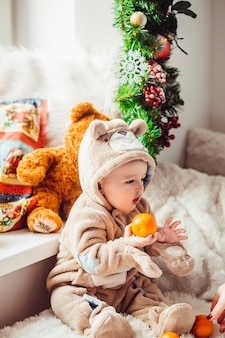 Kleine jongen in beer pak houdt een oranje zittend op de vloer