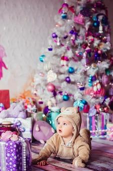 Kleine jongen in beren pak ligt voor een witte kerstboom