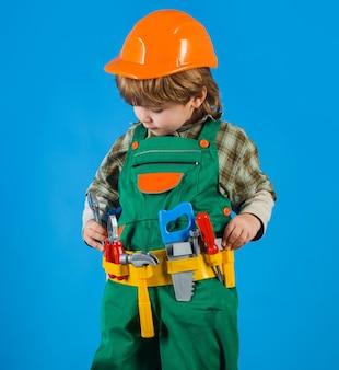 Kleine jongen in bouwers uniform met gereedschapsriem. hulpmiddelen om te bouwen. reparateur voor kinderen. kind spel.