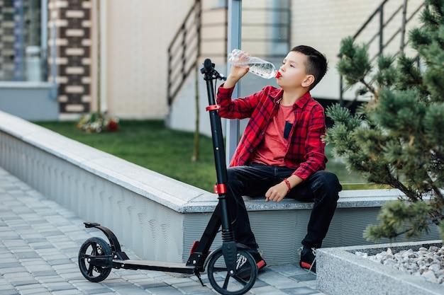 Kleine jongen in casual rood shirt zit in de buurt van zijn scooter en drinkwater.