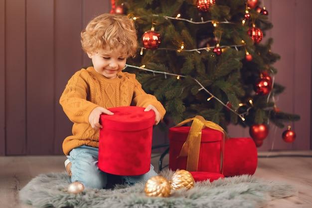 Kleine jongen in de buurt van de kerstboom in een bruine trui