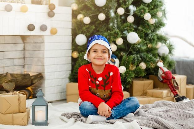 Kleine jongen in de buurt van de kerstboom