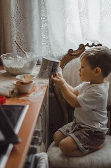 Kleine jongen in de keuken helpt moeder om te koken. het kind is betrokken bij het koken.