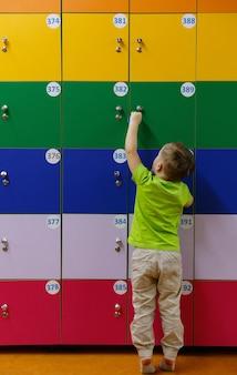 Kleine jongen in de kleedkamer in de buurt van persoonlijke veelkleurige kluisjes. schattige jongen open locker in een kleedkamer achteraanzicht