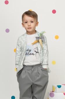 Kleine jongen in de trendy en designer pakken en sneakers op een witte achtergrond