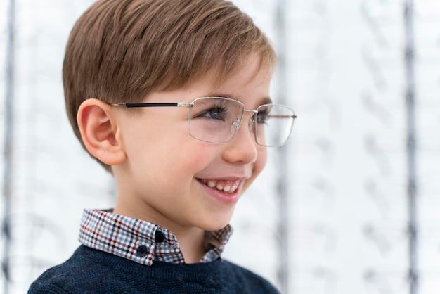 Kleine jongen in de winkel die op een bril probeert