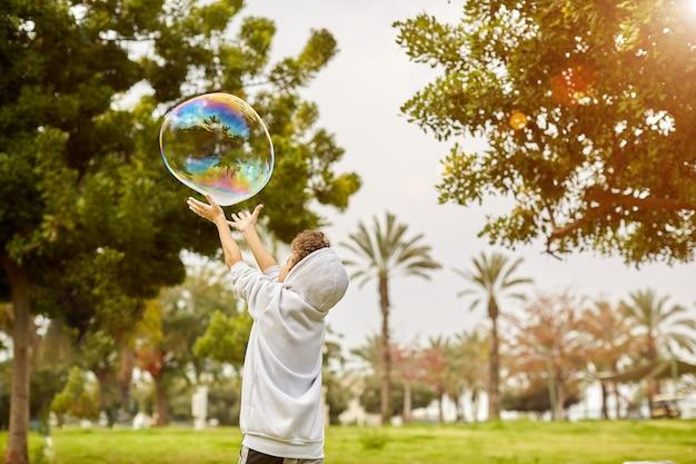 Kleine jongen in de zonsondergang vangt zeepbellen