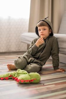 Kleine jongen in dinosaurus kostuum