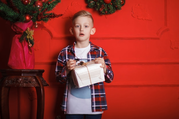 Kleine jongen in een geruit overhemd met een geschenk in zijn handen staat op kerstavond bij de rode muur
