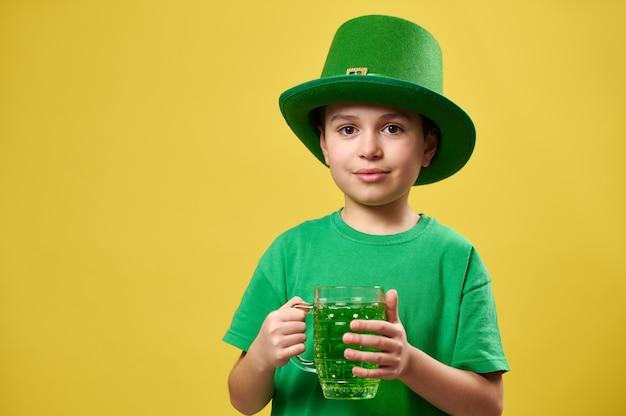 Kleine jongen in een groene ierse kabouter hoed houdt een glas met een groene drank