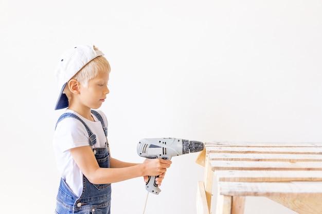 Kleine jongen in een helm speelt in de bouwer met gereedschap