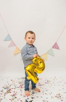 Kleine jongen in een overhemd en broek staat en houdt een gouden folie nummer twee op een witte achtergrond