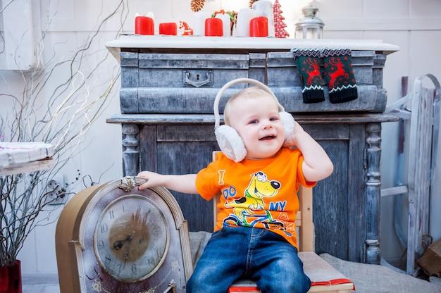 Kleine jongen in een pluizige koptelefoon plezier, lacht, nieuwjaar